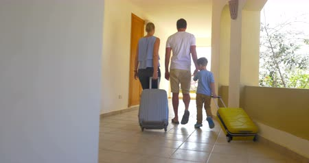 vacation : Steadicam shot of parents and son walking in light hotel corridor. Mother and son rolling travel bags. They leaving or checking in Stock Footage