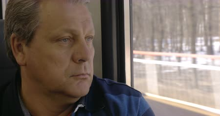 wistful : Close-up shot of a senior man having peaceful time during his travel ride. He staring through the window with thoughtful look