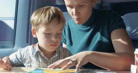 két : Mother and little son spending time with colorful childrens book in train. Mom telling child a story while he looking and pointing at pictures