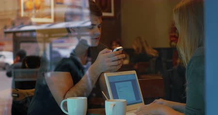 gotículas : Young people busy with their devices duirng tea break in cafe. Man using smart phone and woman typing on laptop. They talking without eye contact Stock Footage