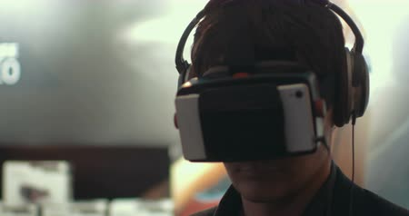 realidade : Close-up shot of a man in headphones getting experience in using VR-headset. Augmented reality device creating virtual space for smartphone applications