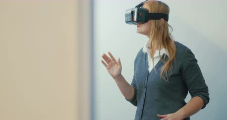 realidade : Young blonde woman playing game using VR-helmet for smart phones. Augmented reality device allows to deep into virtual space Vídeos