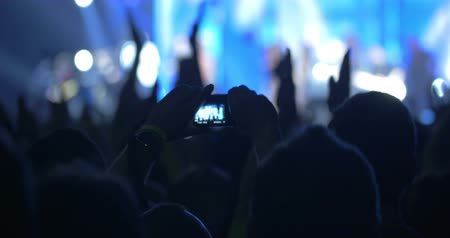 izgatott : Excited viewers applauding to the singer or band performing on colored illuminated stage. One of the fans taking picture or making video with digital camera Stock mozgókép