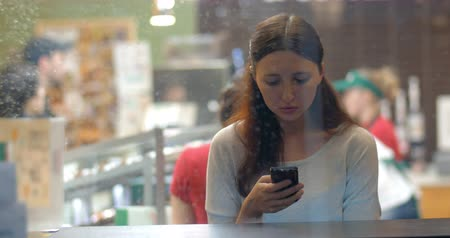 текст : Young woman typing sms or chatting in social network srvice on mobile phone in a cafe