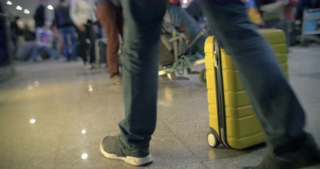 zsák : Yellow roll-on bag on the floor at the crowded airport. Then man taking it and leaving