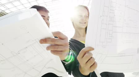 counsel : Slow motion shot of young engineers holding building layouts in hands and discussing them.