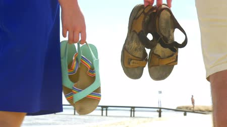 footgear : Steadicam slow motion shot of summer shoes in hands of walking people. Stock Footage