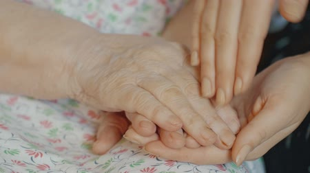 cuidados com o corpo : Slow motion shot of hands of a young person caressing old hands.