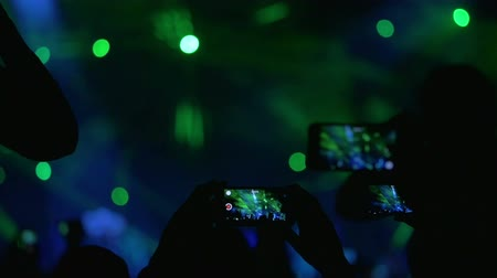 musicians stage : Slow motion shot of people holding smartphones over the heads to shoot the performance on the stage.