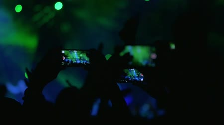 koncert : Slow motion of viewers with smart phones on the concert making video of bright green and blue laser show on the stage Dostupné videozáznamy