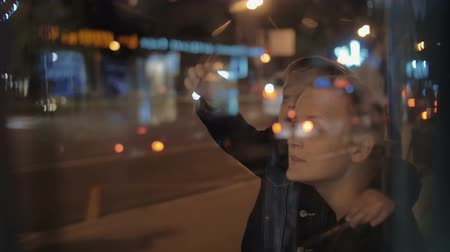 falar : Slow motion of mother and son at bus stop by the road with intense traffic at night. Boy looking into distance and pointing at something. View through the glass