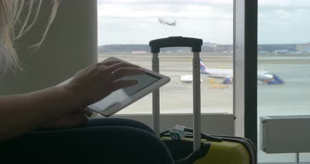 устройство : Female traveler using touch pad sitting by the window at airport, suitcse standing nearby. Takeoff strip with planes in background. One airplane is getting off Стоковые видеозаписи
