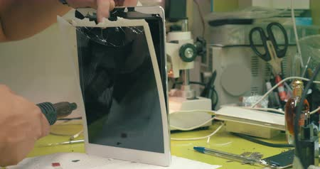 tamiri : Close-up shot of man using special tool to remove broken touchscreen. Tablet computer under repair Stok Video
