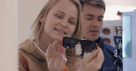optický : Young couple in the store. Woman trying on several sunglasses, man helps to make a good choice. Fashionable accessories