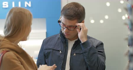 optický : Young couple in optical store. Man trying the glasses for visison correction while woman choosing sunglasses