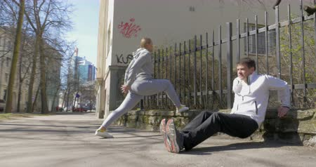 estocolmo : Steadicam shot of young people having outdoor morning training in the city. Woman and man doing exercise on sidewalk in the street Vídeos