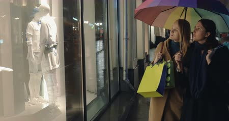 kirakat : Two female friends with colorful umbrella and shopping bags walking along the city street with boutiques. They stopping to look at shop-window with mannequins  and going further