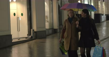 butik : Steadicam shot of young women walking  under colorful umbrella in evening rainy city and having a talk after good shopping Stok Video