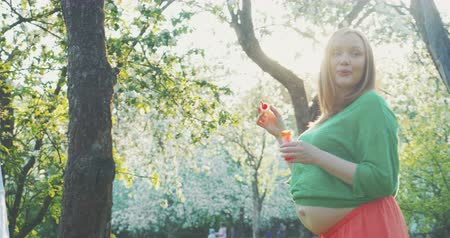 luz do sol : Steadicam shot of pregnant woman walking in garden among blooming trees and blowing soap bubbles.