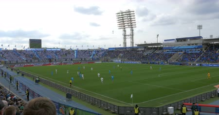 zenit : ST. PETERSBURG, RUSSIA - APRIL 5, 2015: Football match at the stadium. Players having active game on sideline. Fans ob grandstands waving hands Stock Footage