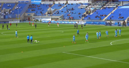 premier : ST. PETERSBURG, RUSSIA - APRIL 5, 2015: Players of both football teams warming-up on the field in stadium, few viewers on stadium stands. Zenit-CSKA football match, Russian Championship,  Premier League