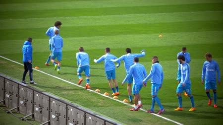zenit : ST. PETERSBURG, RUSSIA - APRIL 5, 2015: Slow motion of football players doing dribbling exercise under the coach supervision. Warming-up before Zenit-CSKA football match, Russian Championship,  Premier League