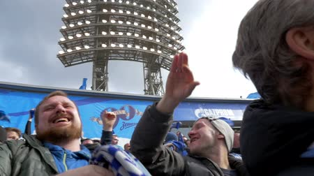 zenit : ST. PETERSBURG, RUSSIA - APRIL 5, 2015: Slow motion of two male fans giving hi-five after the favorite team shooting a goal. One of them waving with blue team scarf with other excited supporters. Zenit-CSKA football match, Russian Championship, Premier Le
