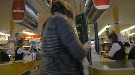 cash free : TALLINN, ESTONIA - APRIL 25, 2015: Slow motion steadicam shot of people at the cash registers of tax free supermarket on board the ferry Tallinn-Stockholm