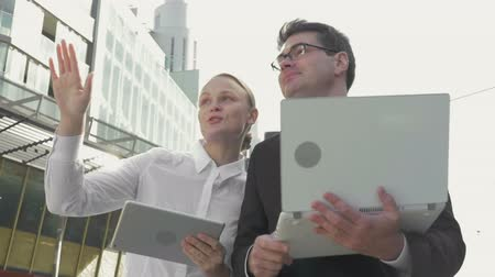 elektronický : Slow motion steadicam shot of two young businesspeople walking in the city. They have business talk and using electronics. Man working with laptop and woman with tablet computer