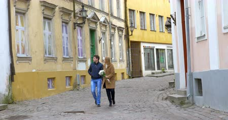 stare miasto : Young romantic couple wandering among ancient houses in Old Town of Stockholm, Sweden. Happy people holding hands, woman carrying white flowers