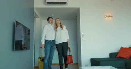 nowe mieszkanie : Steadicam shot of young family couple moving into the new house. Husband with rolling bag and wife entering the room and enjoying the view of apartment. Dreams come true concept Wideo