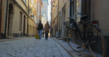 historical building : Steadicam low angle shot of a tourist couple having a walk in old European street in Stockholm. Bike in foreground with view to the historic building at the end