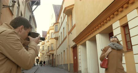 macskaköves : Steadicam shot of young man and woman making video with retro camera. Happy woman posing among the ancient buildings and man filming