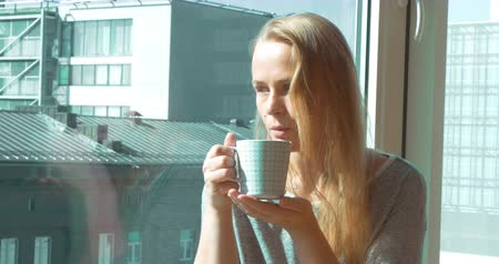 herbata : Steadicam shot of a young woman sitting on the windowsill with a cup of tea. Shes drinking the beverage and looking out the window.