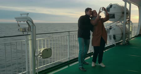 круиз : Young happy couple is taking selfie at smartphone being on the deck of ferry.