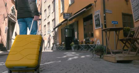 dava : Steadicam shot of a traveling man walking on the narrow streets of the old part of the city with yellow suitcase on wheels. Visible only feet, no face, body part. Stockholm, Sweden