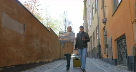 Steadicam shot of a couple of travelers with map sightseeing during their journey. Stockholm, Sweden