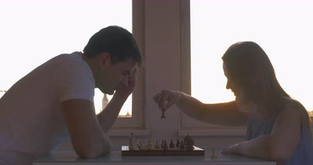 iyi olmak : Young man and woman playing chess at home. Sunset can be seen in the window. Logic board game is a good way to spend th evening Stok Video