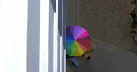 andar : Steadicam high angle shot of a couple walking in the street under rainbow colored umbrella Vídeos