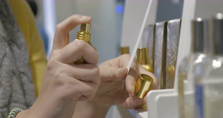 perfume bottle : Woman taking gold bottle and  squirting essence out on the tester
