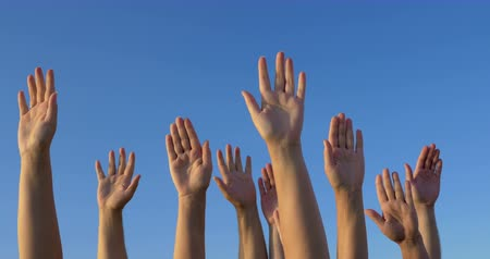 dobrovolník : Male and female hands raised and held up on the background of clear blue sky. Solid vote or volunteers