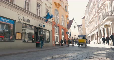 kolo : TALLINN, ESTONIA - APRIL 27, 2015: Steadicam shot of moving along the street with old buildings of classical European architecture on sunny day. People walking and bike taxi riding there