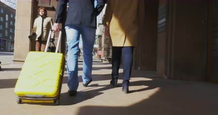 podróżnik : TALLINN, ESTONIA - APRIL 22, 2015: Steadicam shot of a couple of tourists walking along the street. Man is rolling yellow trolley bag. Wideo