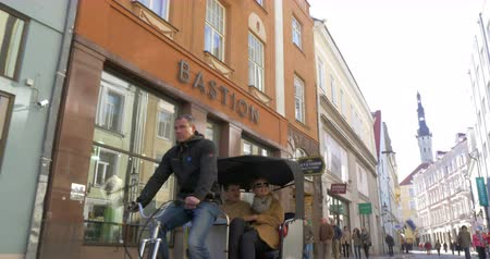 transportar : TALLINN, ESTONIA - APRIL 27, 2015: Steadicam shot of a bike taxi carrying two tourists along the streets of Tallinn. Stock Footage