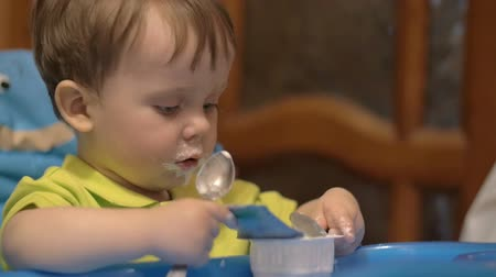 acabamento : Slow motion shot of a little boy in high chair finished eating food with spoon. Stock Footage