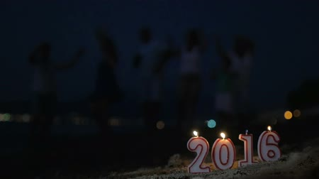 família : Slow motion clip of lit 2016 candles on the sand, blurred family celebrating the holiday at the seaside in background. New Year and Christmas time Vídeos