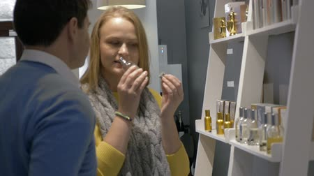perfume bottle : Man and woman are standing by the shelf in perfumery shop. They are trying fragrance with paper tester. Stock Footage