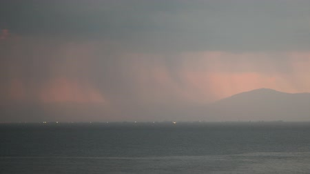 costa : Timelapse shot of thunderstorm. Rain pouring from heavy clouds and lightnings striking over the coastal city and sea