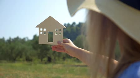 ипотека : Slow motion of a woman in summer hat holding wooden house model on the background of green forest and blue sky. Concept of eco or country house, real estate and mortgage Стоковые видеозаписи
