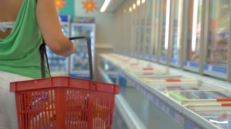 lodówka : Slow motion of a woman with shopping cart walking along the refrigerators in the supermarket. Buying frozen products